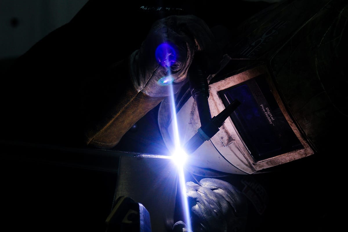 Welder with torch working on custom sheet metal fabrication project